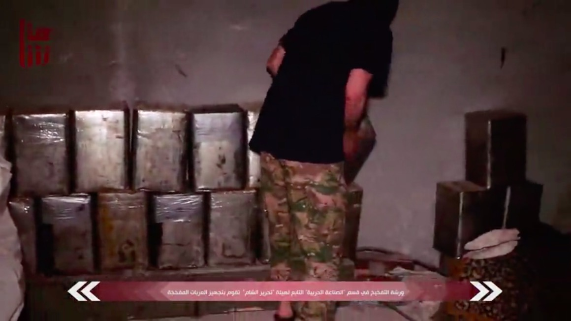 An HTS SVBIED workshop worker lifting up IEDs and carrying them to an SVBIED. From a June 2020 Shamna video release.