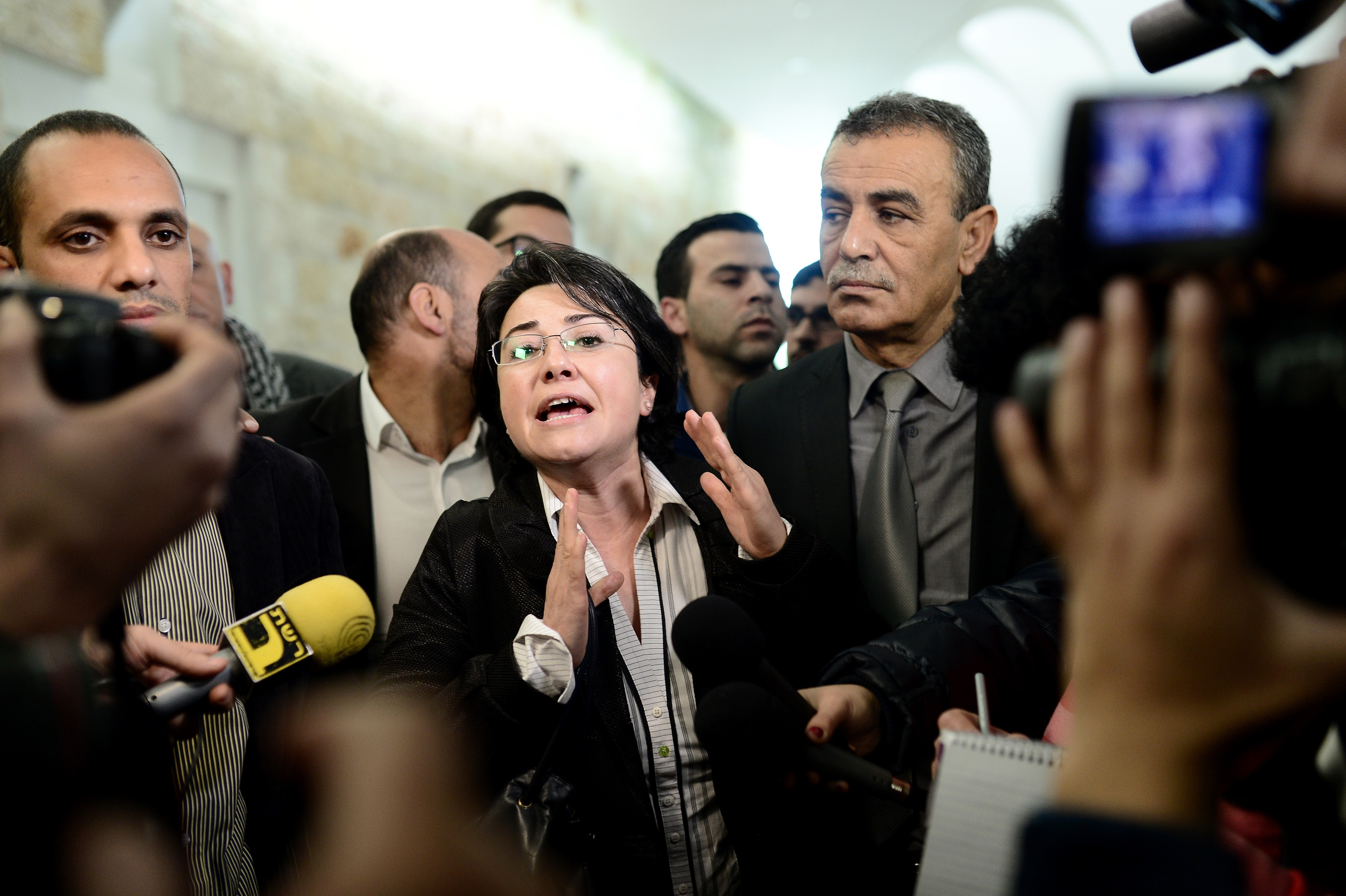Arab member of Israel's Knesset Haneen Zoabi (C) speaks to the press after the court decision about Israels ban of Arab lawmaker Zoabi from election in Jerusalem on February 14, 2015.
