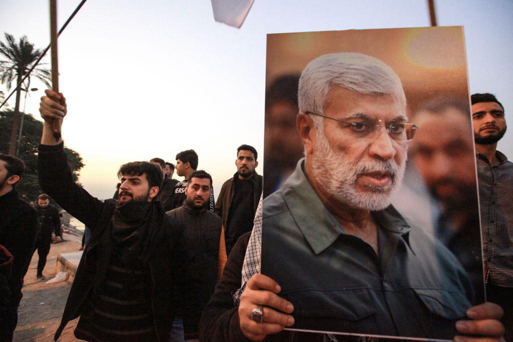 Supporters of the predominantly Shia Muslim Popular Mobilization Forces (PMF) gather with flags and posters of the PMF deputy head Abu Mahdi al-Muhandis during an anti-US protest after the US airstrike in Baghdad