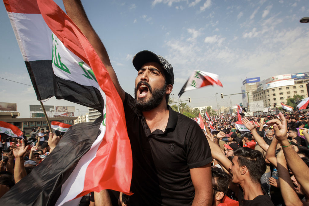 Protesters shout slogans during an anti-government demonstration about the provision of jobs and alleged government corruption, in Tahrir Square in central Baghdad, October 1, 2019 (Photo by Ameer Al Mohammedaw/picture alliance via Getty Images)