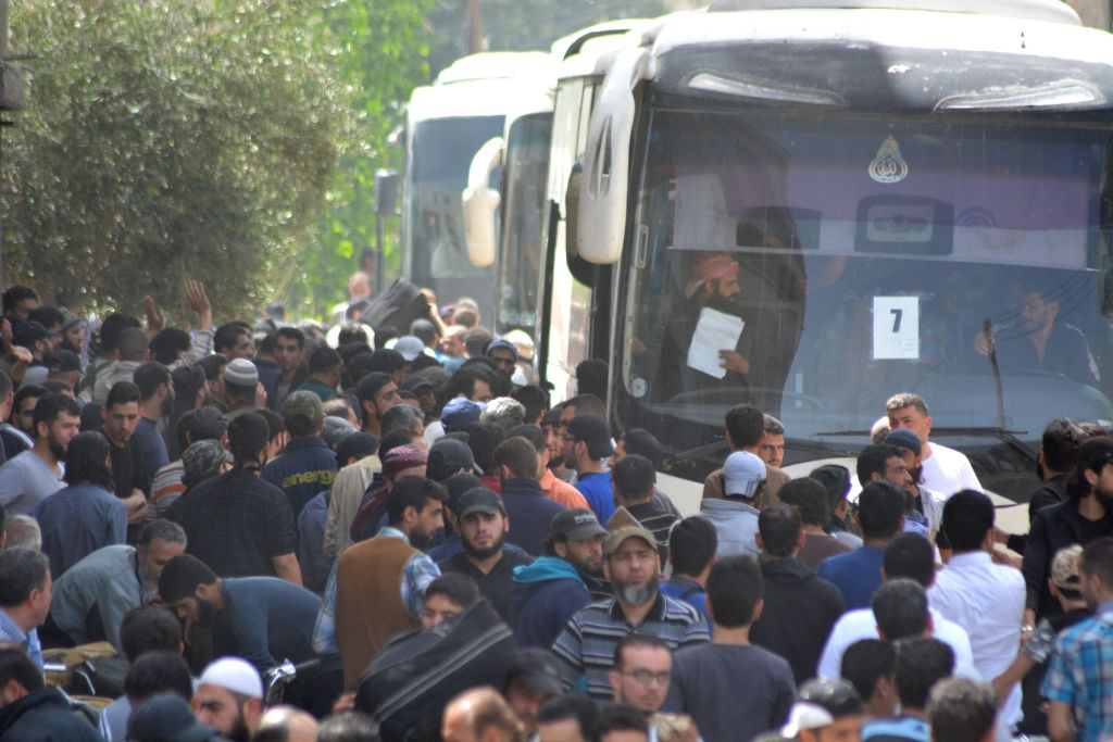 Members of the Free Syrian Army (FSA) and civilians get on the busses to be evacuated from the FSA controlled area of Yarmouk Camp in southern Damascus under the Yarmouk camp evacuation agreement, as part of the compulsory evacuation as agreed on April 29, in Damascus, Syria on May 03, 2018. A deal has been struck between the Syrian regime and the Tahrir al-Sham group to evacuate areas controlled by the latter in the Yarmouk Palestinian refugee camp near Damascus. (Photo by Rami Alsayed/Anadolu Agency/Getty Images)