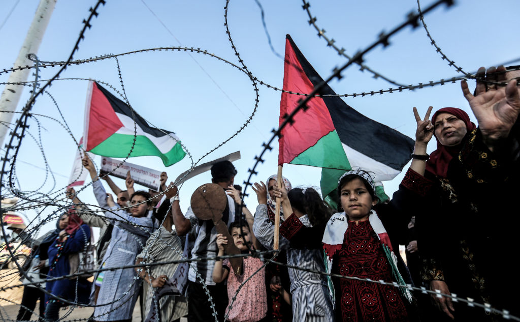 "A girl raises a Palestinian flag as another Palestinian boy holds a wooden key symbolising the return, as they stand with others before the barbed-wire marking the border between the Gaza strip and Israel east of Gaza City on May 13, 2018 during a demonstration anticipating the 70 years since the Palestinian ""Nakba"", or catastrophe, of 1948 when over 700,000 Palestinians fled or were expelled from their homes in the 1948 war surrounding Israel's creation. (Photo by MAHMUD HAMS / AFP) (Photo credit should read MAHMUD HAMS/AFP via Getty Images)"