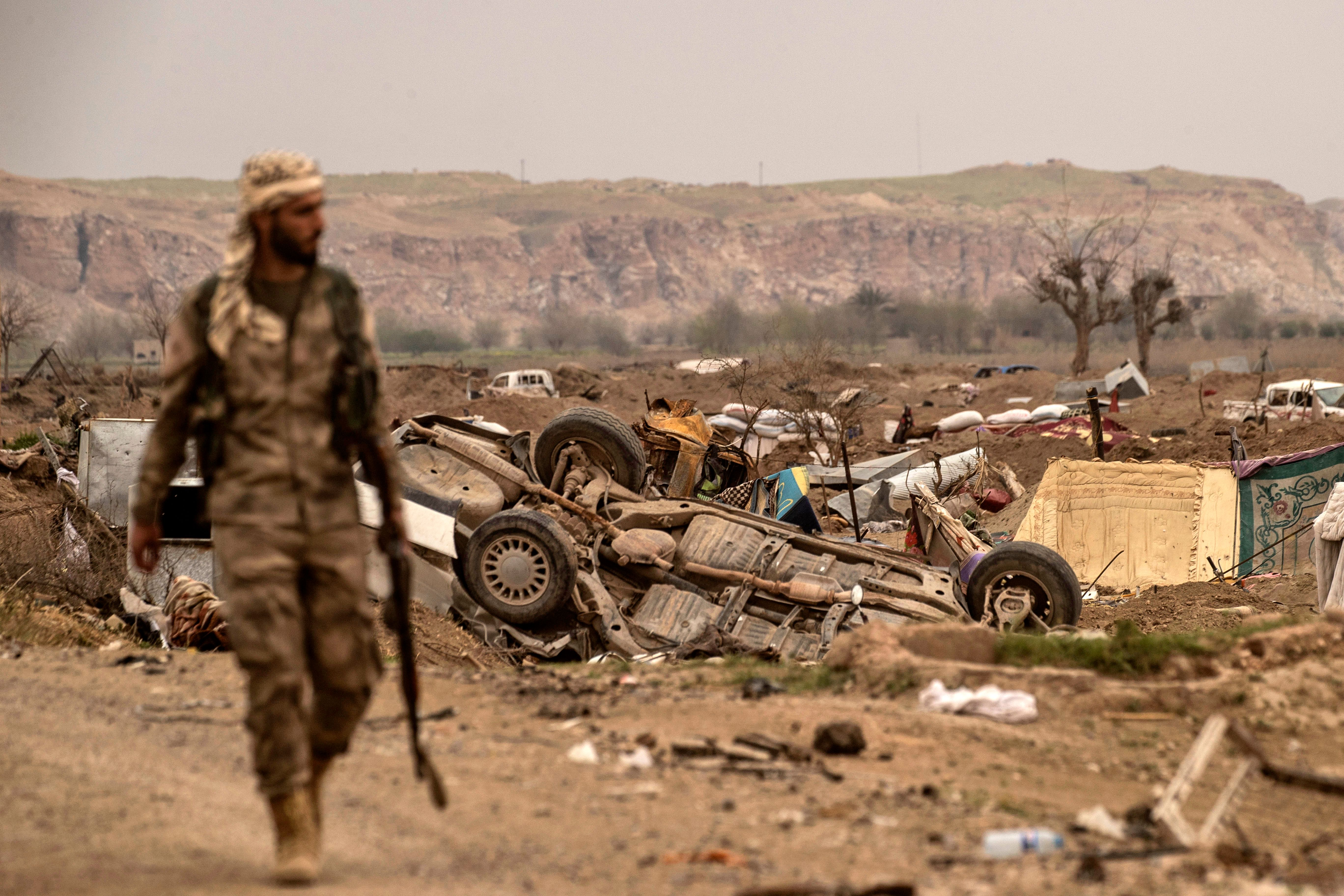 """A member of the SDF walks past damaged vehicles on the side of a road in the village of Baghouz in Syria's eastern Deir ez-Zor Province on March 24, 2019, a day after the ISIS """"caliphate"""" was declared defeated. Photo by DELIL SOULEIMAN/AFP via Getty Images."""
