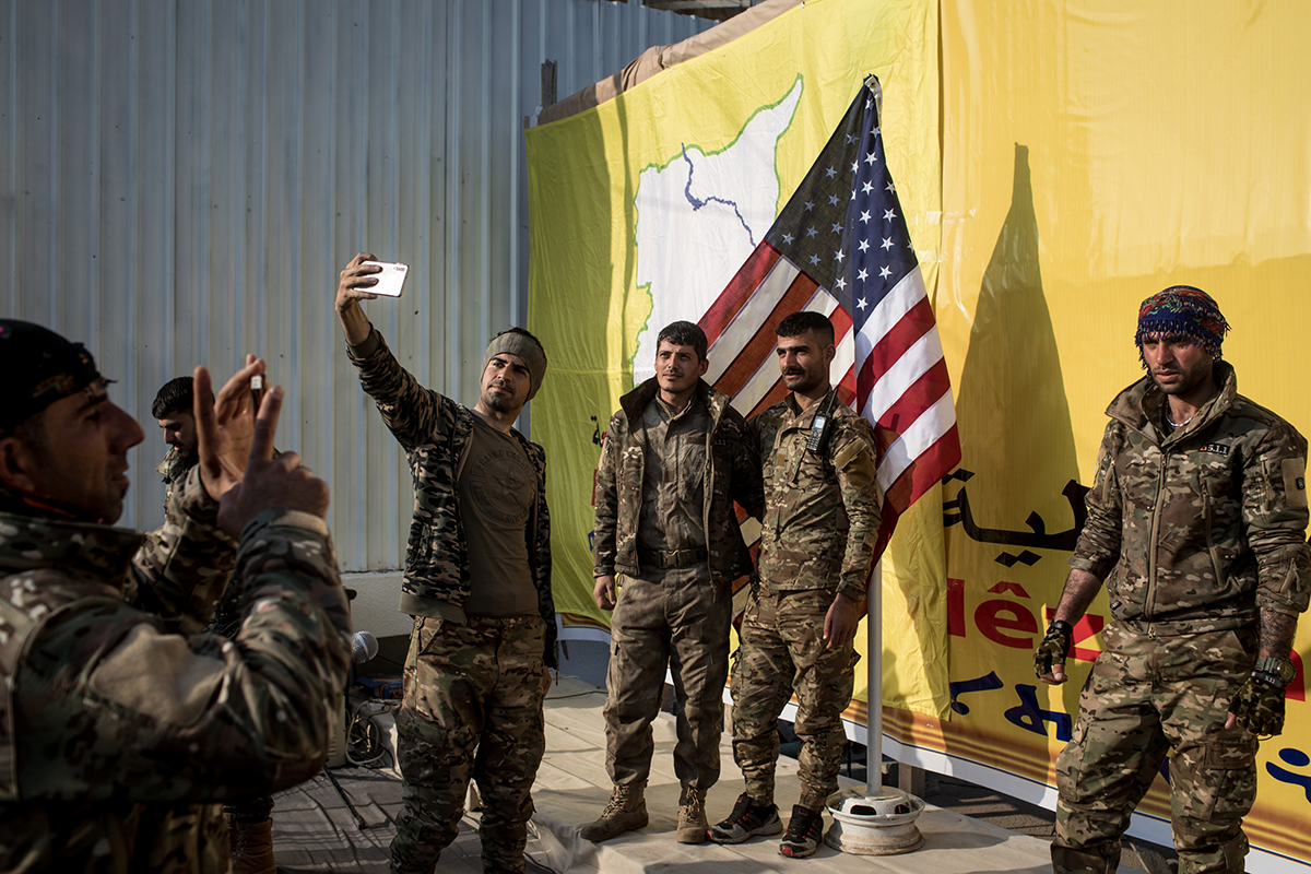SDF fighters pose for a photo with the American flag on stage after a SDF victory ceremony announcing the defeat of ISIL in Baghouz was held at Omer Oil Field on March 23, 2019 in Baghouz, Syria. (Photo by Chris McGrath/Getty Images.)