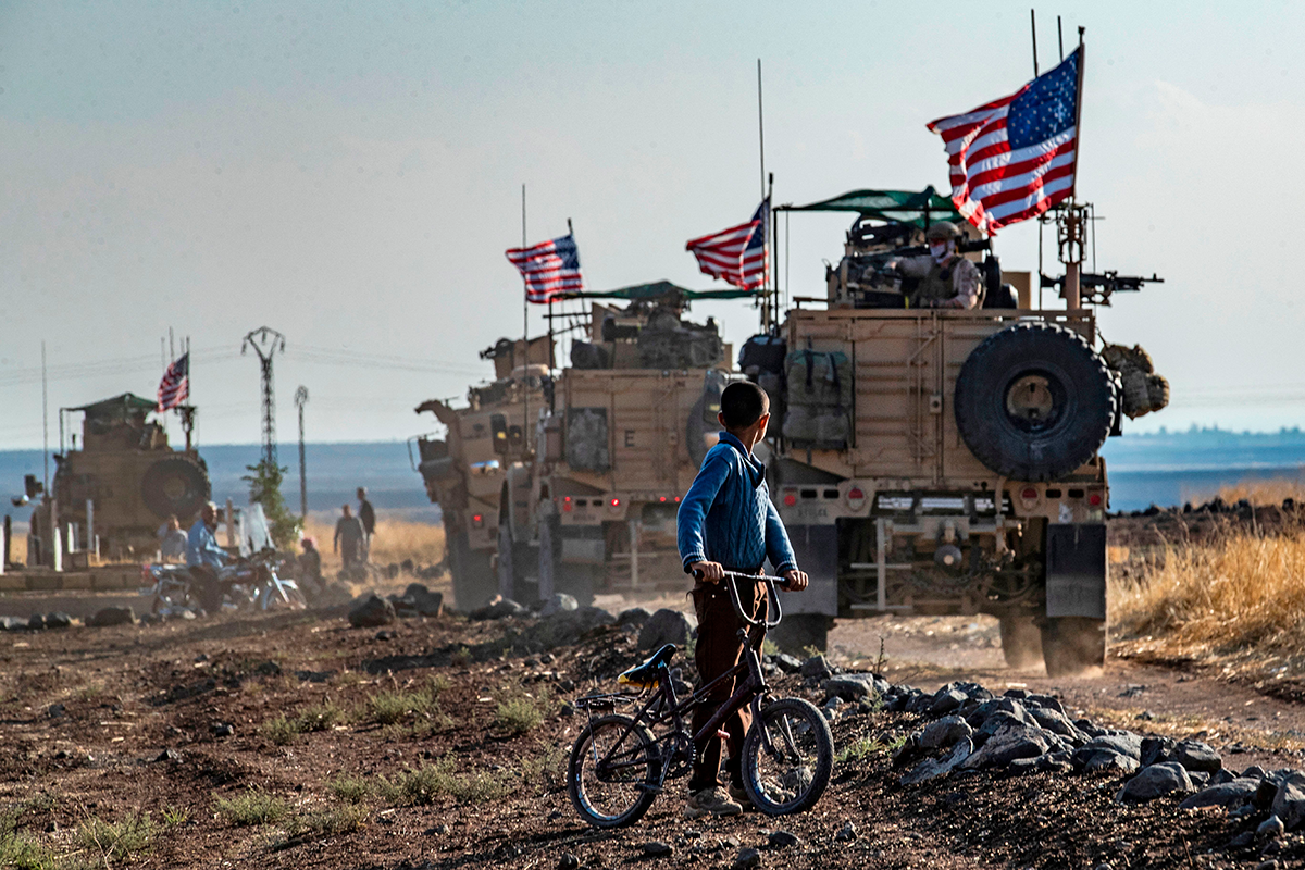 A Syrian boy on his bicycle looks at a convoy of US armored vehicles patrolling fields near the northeastern town of Qahtaniyah at the border with Turkey, on October 31, 2019. (Photo by DELIL SOULEIMAN/AFP via Getty Images.)