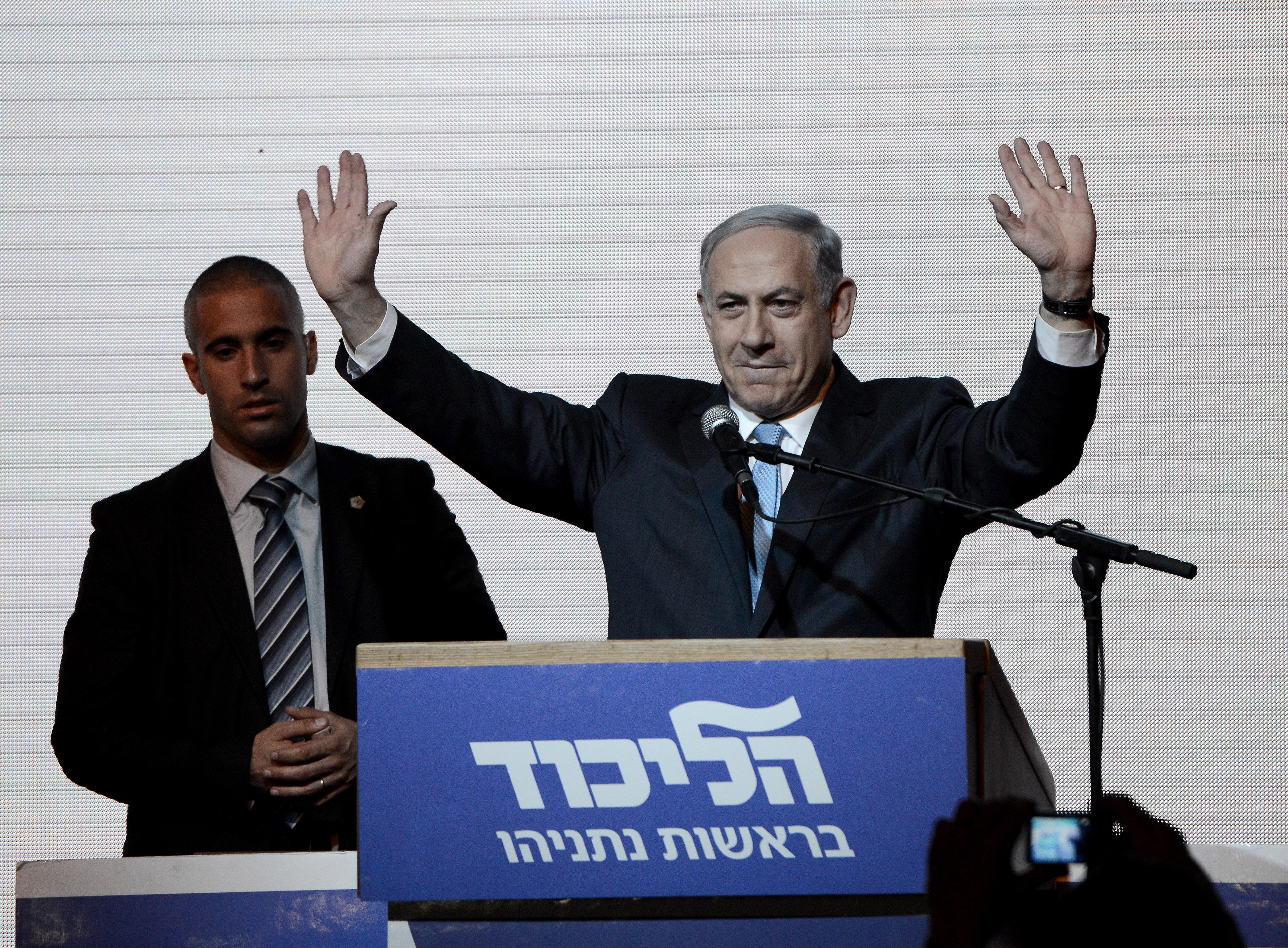 Israeli Prime Minister and the leader of the Likud Party Benjamin Netanyahu greets supporters at the party's election headquarters after the first results of the Israeli general election on March 18, 2015