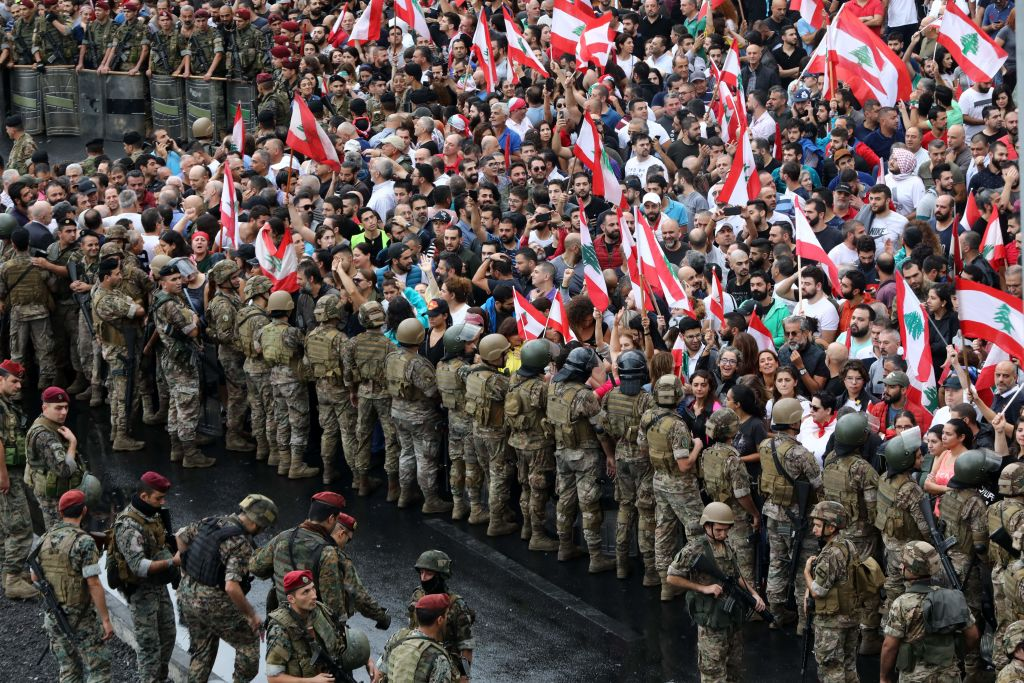 Anti-government protesters facing Lebanese army soldiers wave national flags in the area of Jal al-Dib in the northern outskirts of the Lebanese capital Beirut, on October 23, 2019.