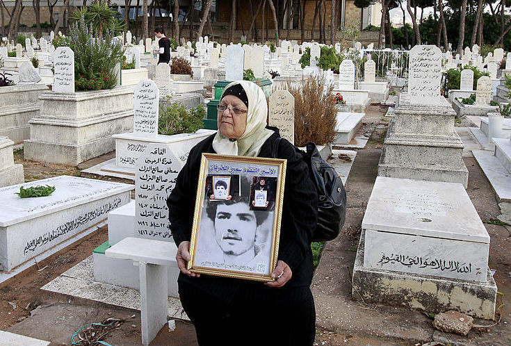A Lebanese women holds an image of her missing son in a cemetery in the Beirut southern suburb of Qasqas on November 17, 2012 which is one of three neighbourhoods where the Lebanese state has recognised the presence of mass graves. (Photo by ANWAR AMRO/AFP via Getty Images)