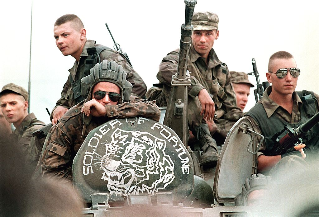 "Members of the Russian Army sit atop an armored personal vehicle with a logo of ""Soldier of Fortune"" 18 July 1995 in Grozny."