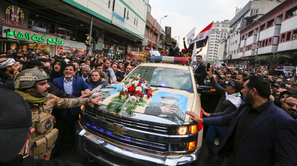 Mourners surround a car carrying the coffins of Iranian military commander Qasem Soleimani and Iraqi paramilitary chief Abu Mahdi al-Muhandis, killed in a US air strike, during their funeral procession in Kadhimiya, a Shiite pilgrimage district of Baghdad, on January 4, 2020.