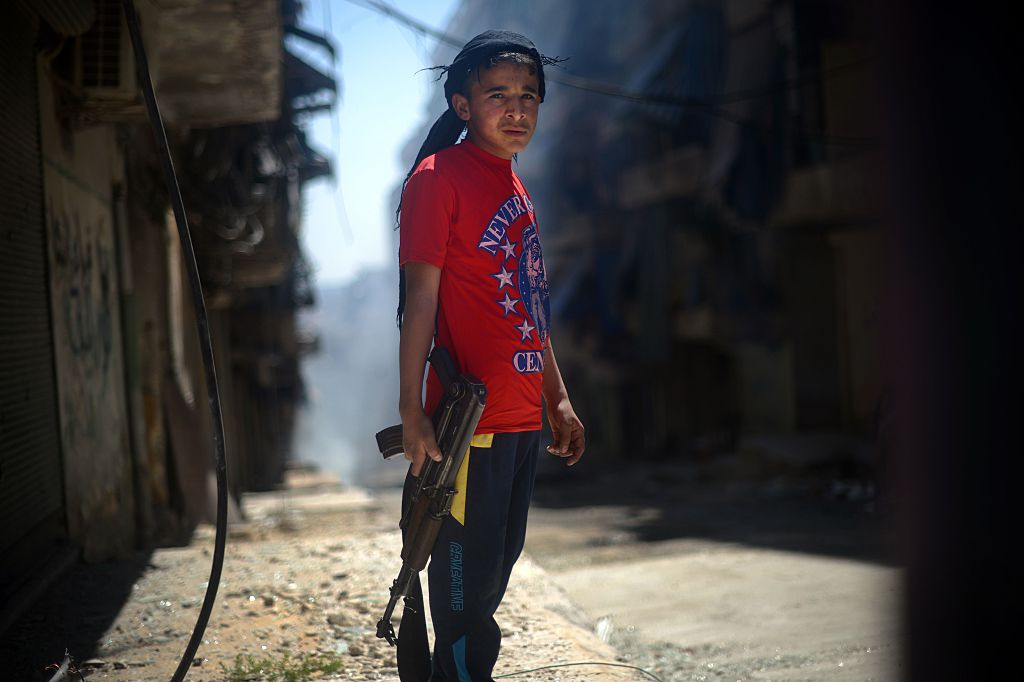 A Syrian boy holds an AK-47 assault rifle in the majority-Kurdish Sheikh Maqsud district of the northern Syrian city of Aleppo on April 14, 2013. (Photo by DIMITAR DILKOFF/AFP via Getty Images)