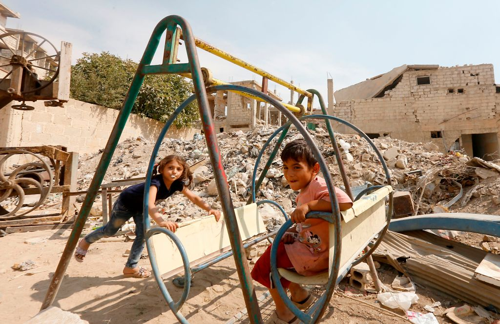Syrian children play amidst badly damaged buildings in Zabdin, in the eastern Ghouta region on the outskirts of Damascus, on October 08, 2018.