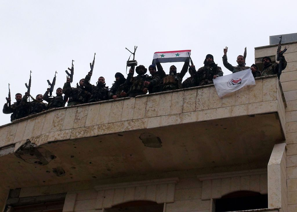 Forces loyal to the Syrian regime celebrate with national flags after Syria's army and allied forces took full control from rebel groups of the strategic town of Salma. Photo credit: STRINGER/AFP/Getty Images.