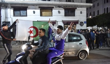 An Algerian flashes the victory gesture while seated on a scooter as another two hold a national flag behind him during a demonstration in the centre of the capital Algiers on March 11, 2019, after President Abdelaziz Bouteflika announced his withdrawal from a bid to win another term in office and postponed an April 18 election, following weeks of protests against his candidacy.