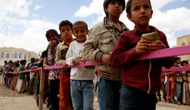 Yemeni children queue to obtain dinner meal distributed as aids by a local charity, the Amalona organization, on May 18, 2019 in Sana'a, Yemen.