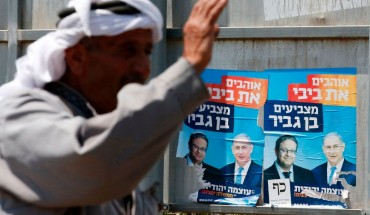 palestinian man in front of israeli election posters