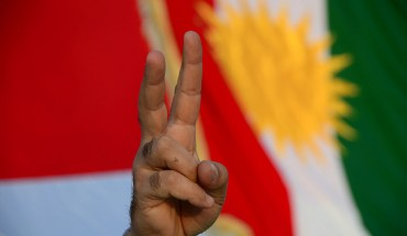 "A demonstrator makes the ""victory"" sign standing in front of a Kurdish flag."