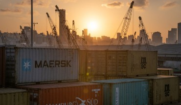The sun sets behind the urban skyline as port cranes and shipping containers sit in an industrial transport area in Beirut, Lebanon, on 11 October 2019.