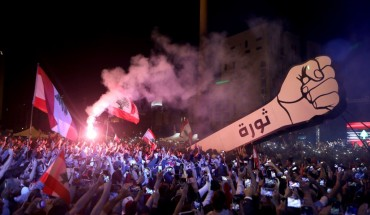 "Lebanese demonstrators raise a new giant sign of a fist that bears the Arabic word ""revolution"" on it, in the Lebanese capital Beirut's Martyr's Square on November 22, 2019, after the sign was burnt overnight by unknown perpetrators."