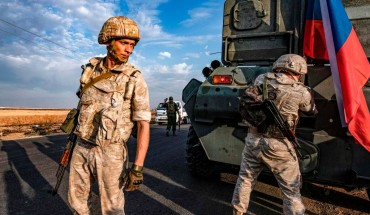 TOPSHOT - Russian military police members stand outside an armoured personnel carrier (APC) along a road in the countryside near the northeastern Syrian town of Amuda in Hasakeh province on October 24, 2019, as part of a joint patrol between Russian forces and Syrian Kurdish Asayish internal security forces near the border with Turkey. - Russian forces have started patrols along the flashpoint frontier, filling the vacuum left by a US troop withdrawal that effectively returned a third of the country to the