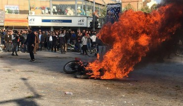 Iranian protesters gather around a burning motorcycle during a demonstration against an increase in gasoline prices in the central city of Isfahan, on November 16, 2019.