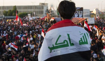 An Iraqi protester deaped in his national flag takes part in an anti-government protest in the southern city of Basra on November 1, 2019.