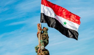 Syrian government soldiers climb up a wooden pole with a Syrian government national flag while deploying for the first time in the eastern countryside of the city of Qamishli in the northeastern Hasakah province on November 5, 2019.