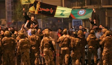 Supporters of Lebanese Shiite groups Hezbollah and Amal wave flags and chant in front of army soldiers in the capital Beirut, on November 25, 2019.