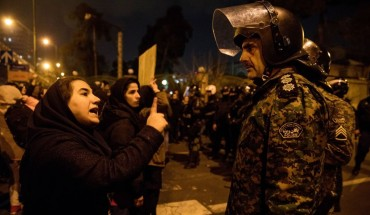 A woman attending a candlelight vigil, in memory of the victims of Ukraine International Airlines Boeing 737, talks to a policeman following the gathering in front of the Amirkabir University in the Iranian capital Tehran on January 11, 2020.