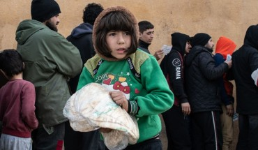 A displaced Syrian girl carries a bag of bread in a stadium which has been turned into a makeshift refugee shelter on February 19, 2020 in Idlib, Syria.