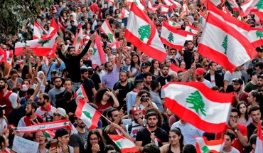 Lebanese protesters wave national flags during demonstrations to demand better living conditions and the ouster of a cast of politicians who have monopolised power and influence for decades, on October 21, 2019 in downtown Beirut. -