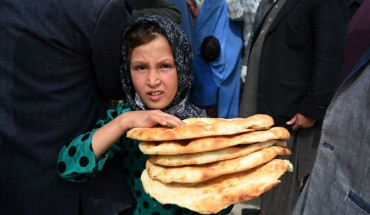 Young Afghan girl holding bread.