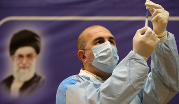 An Iranian medical personnel fills a syringe with the Russian Sputnik-V vaccine, The first registered vaccine against COVID-19, while standing next to a portrait of Irans Supreme Leader Ayatollah Ali Khamenei during a ceremony of initiation of general vaccination against the new coronavirus disease, in a hospital in western Tehran on February 9, 2021. (Photo by Morteza Nikoubazl/NurPhoto via Getty Images)