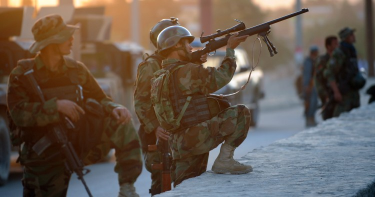 An Afghan soldier aims his gun as he guards the area surrounding the Intercontinental hotel during a military operation against Taliban militants that stormed the hotel in Kabul on June 29, 2011.