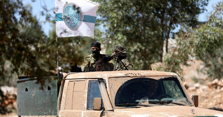 Syrian fighters stand at the back of a pick-up as they attend a mock battle in anticipation of an attack by the regime on Idlib province and the surrounding countryside, during a graduation of new Hayat Tahrir al-Sham (HTS) members at a camp in the countryside of the northern Idlib province.