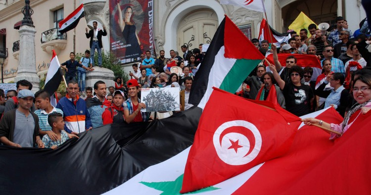 Tunisian protestors wave their national and the Syrian flags on May 6, 2013.