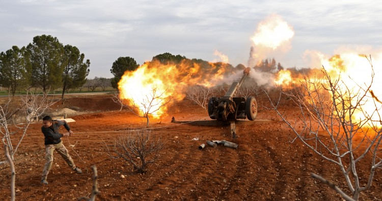 An opposition fighter fires a gun from a village near al-Tamanah during ongoing battles with government forces in Syria's Idlib province on January 11, 2018