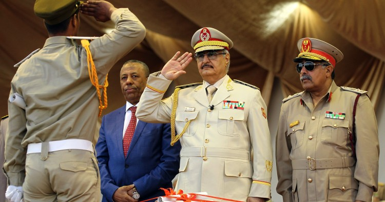 Libyan Strongman Khalifa Haftar salutes next to Libyan National Army's Chief Of Staff Abdelrazak al-Nadhuri and Libyan former prime minister Abdullah al-Thani.