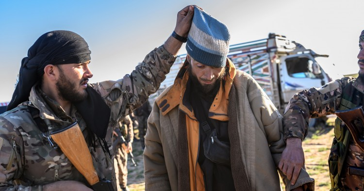 A member of the SDF raises the hood of a Bosnian man suspected of being an ISIS fighter as he is searched after leaving the group's last holdout of Baghouz, on March 1, 2019.