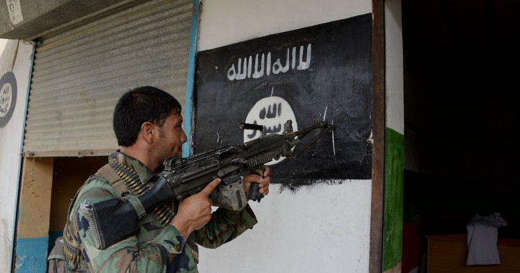 An Afghan soldier points his gun at an ISIS banner as he patrols in Nangarhar Province
