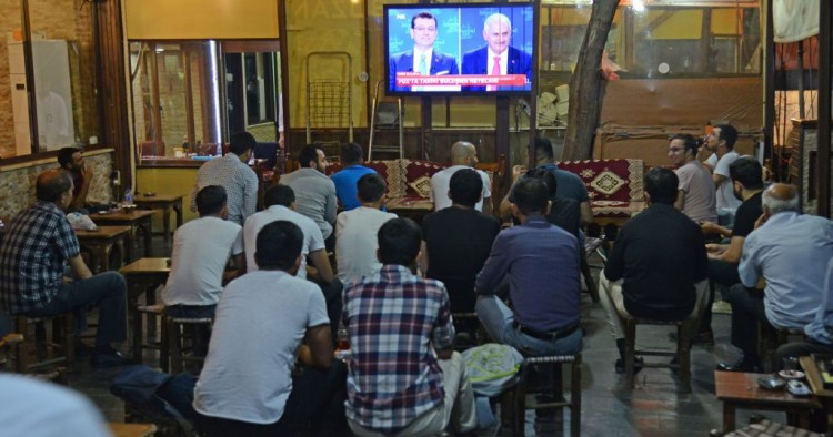 People watch a live broadcast of a televised debate between Istanbul's mayoral candidate Binali Yildirim (R) of Turkey's ruling AKP, and Istanbul's deposed mayor Ekrem Imamoglu (L) of the CHP, is shown on a screen at a tea house in Diyarbakir on June 16, 2019.