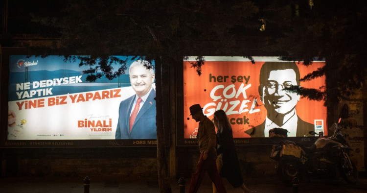 People walk past election posters of AK Parti candidate Binali Yildirim (L) and CHP Party, candidate Ekrem Imamoglu (R) during campaigning in the re-run of the Istanbul mayoral election on June 01, 2019 in Istanbul, Turkey.
