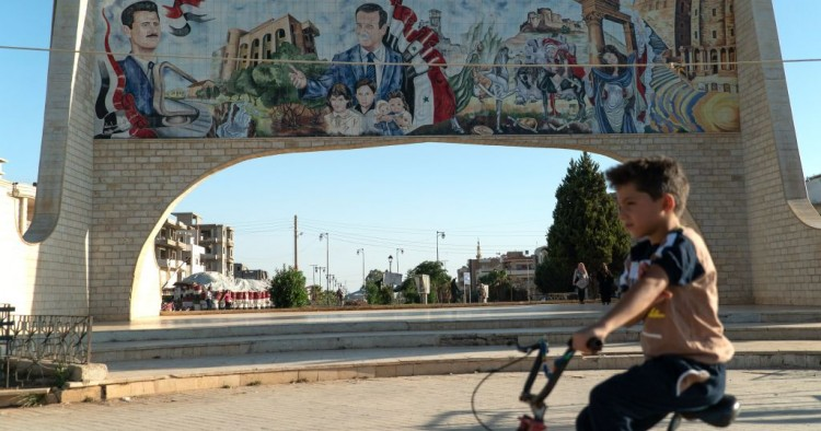 A young boy rides his bicycle in the southern Syrian city of Daraa on August 14, 2018. Behind him is a gate ornated with images of Syrian President Bashar al-Assad (L) and his late father Hafez al-Assad. (Photo by Andrei BORODULIN / AFP) (Photo credit should read ANDREI BORODULIN/AFP/Getty Images)