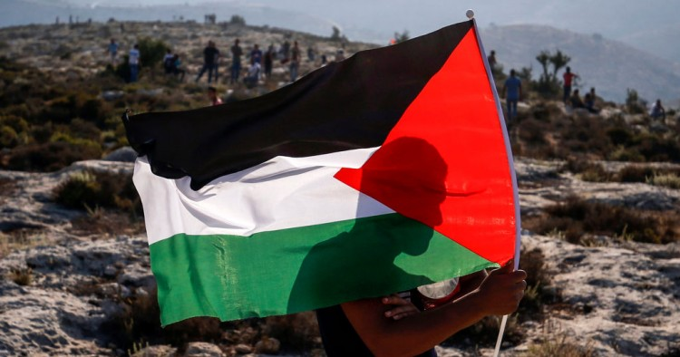 A Palestinian protester waves a Palestinian flag during a demonstration in the village of Ras Karkar west of Ramallah in the occupied West Bank on September 4, 2018.