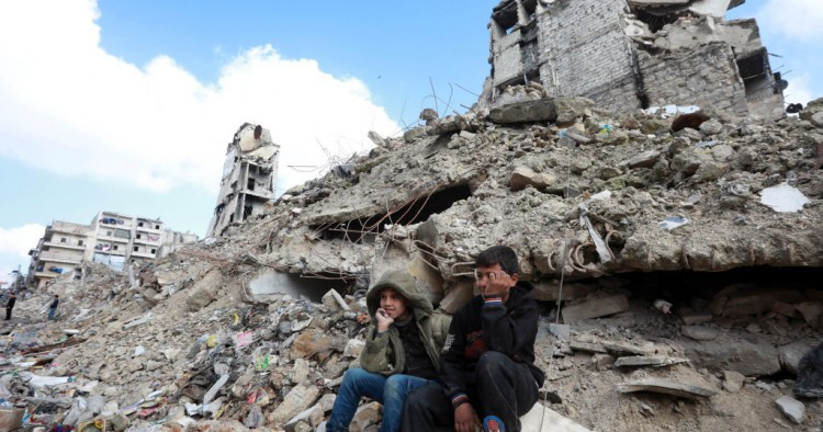 Children sit on the rubble of buildings in Aleppo, Syria.