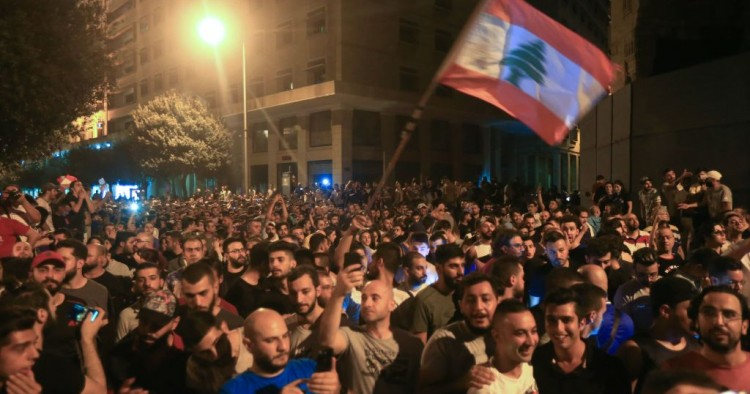 Demonstrators wave a flag during a protest against a government decision to tax calls made on messaging applications on October 17, 2019 outside the government palace in Beirut.