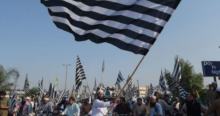 "An activists of the Jamiat Ulema-e-Islam waves the party flag during the anti-government ""Azadi March"" towards Islamabad, in Peshawar on October 27, 2019."