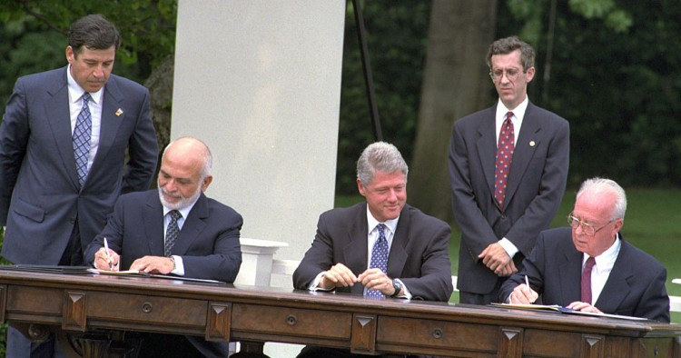 The Israel-Jordan peace treaty being signed in 1994. US President Bill Clinton watches Jordan's King Hussein and Israeli Prime Minister Yitzhak Rabin sign the treaty on the White house lawn