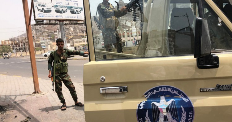 A fighter of the UAE-trained Security Belt Force, dominated by backers of the the Southern Transitional Council (STC) which seeks independence for south Yemen, mans the turret of a technical (pickup truck mounted with an anti-aircraft gun) displaying portraits of separatist leader Aidarus al-Zubaidi and showing the logo of the STC, in the Crater district in the centre of Yemen's second city of Aden on August 12, 2019.