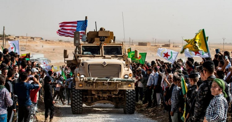 Syrian Kurds gather around a US armoured vehicle during a demonstration against Turkish threats next to a US-led international coalition base on the outskirts of Ras al-Ain town in Syria's Hasakeh province near the Turkish border on October 6, 2019.